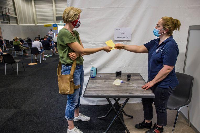 Een vrouw in Barendrecht laat een bewijs van haar coronavaccinatie in haar gele boekje stempelen. Beeld Arie Kievit