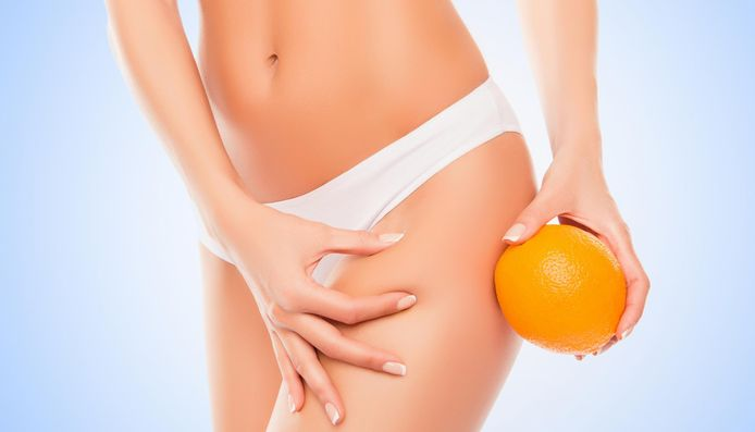 Woman in white panties holding orange near hip and checking fat on leg