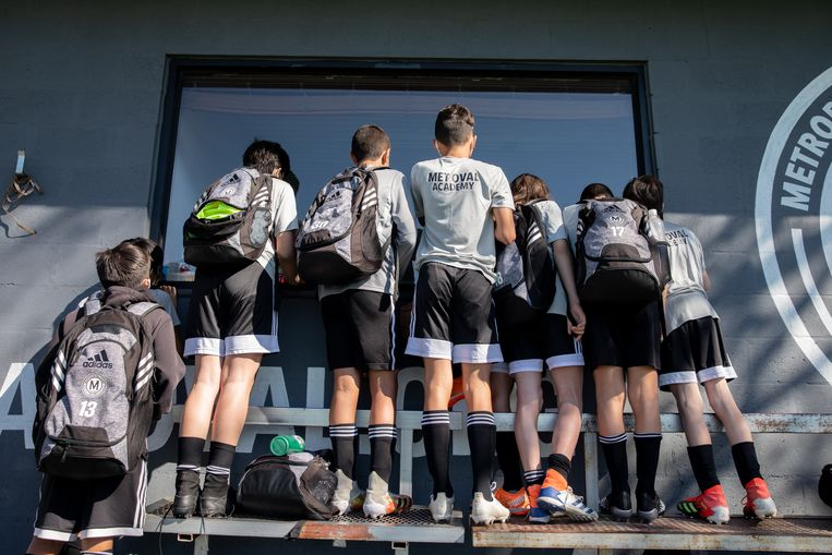 Pupillen van Metropolitan Oval, een voetbalschool in Queens, verdringen zich om iets te zien van een Champions League-wedstrijd. Beeld Jackie Molloy