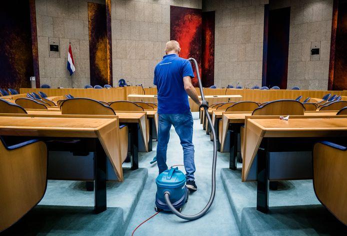Een schoonmaker in de plenaire zaal van de Tweede Kamer. In de schoonmaak geldt voor de meeste mensen het minimumloon van 10,21 euro. Onvoldoende, stelt de FNV.