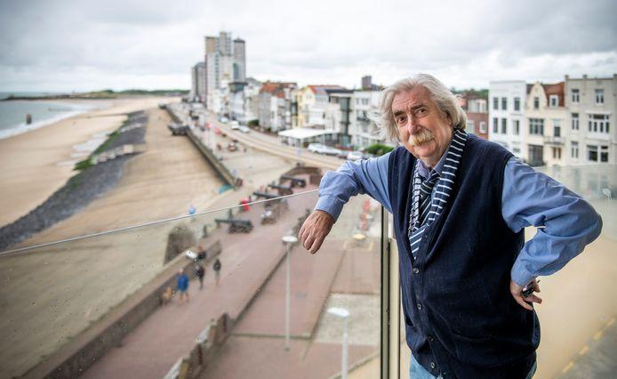 """Kunstenaar Rien Verschuur op het balkon zijn tijdelijke onderkomen op de boulevard in Vlissingen. ,,Dit is het voorportaal van de hemel, omdat per kwartier het licht hier verandert."""""""