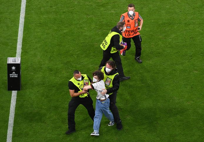 A protestor is taken from the pitch by security after he ran onto the field holding a Rainbow Flag and stood in front of the Hungarian team during Hungary's national anthem before the Euro 2020 soccer championship group F match between Germany and Hungary at the football arena stadium in Munich, Germany, Wednesday, June 23, 2021. (Matthias Hangst/Pool Photo via AP)