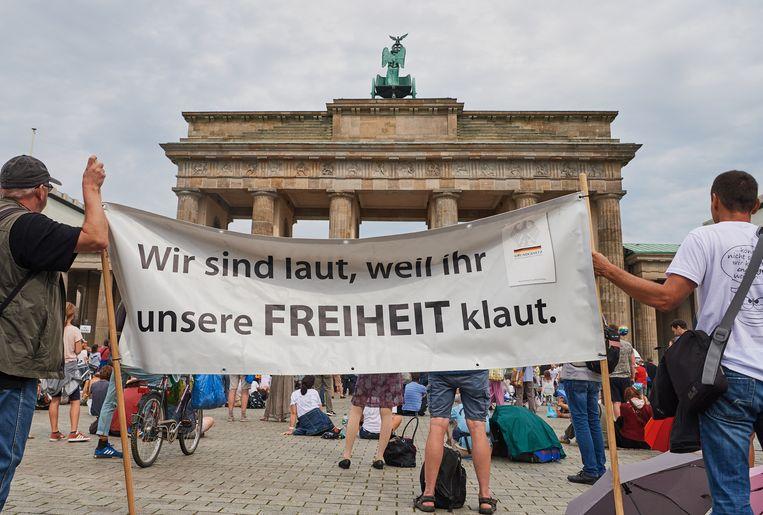 Demonstranten in Berlijn met een spandoek: 'Wij zijn luid omdat jullie onze vrijheid stelen.' Beeld Annette Riedl / DPA