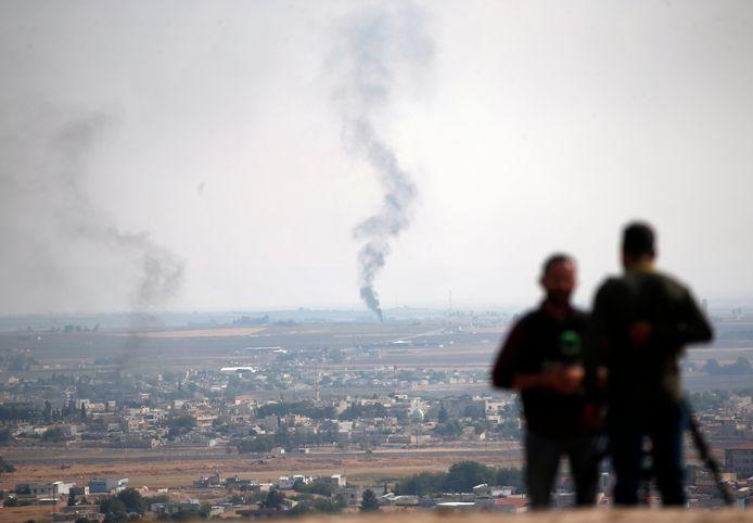 Journalisten maken reportages vanaf een heuvel in de Turkse grensstad Ceylanpinar. Op de achtergrond de Syrische stad Ras al-Ayn.