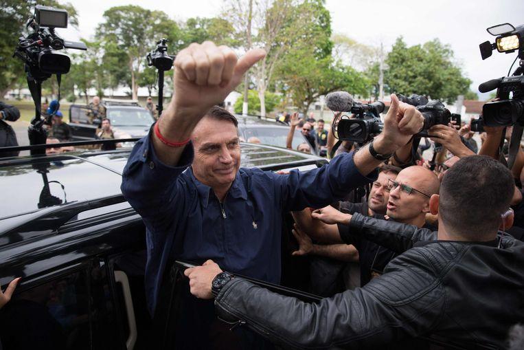 De extreemrechtse presidentskandidaat Jair Bolsonaro begroet zijn aanhangers na het uitbrengen van zijn stem in Rio de Janeiro. Beeld AFP