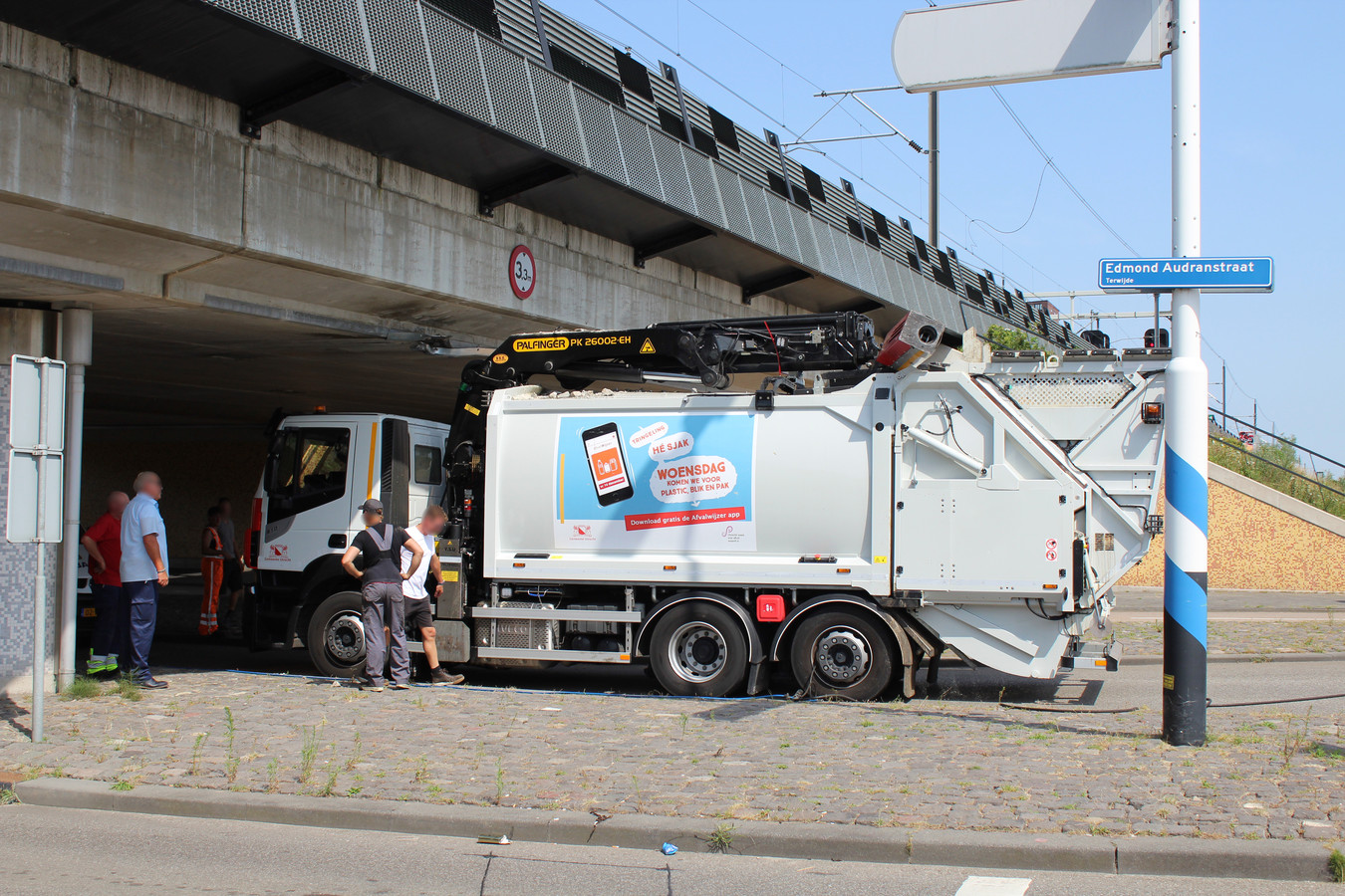 Een vuilnisauto boort zich vast onder het spoorviaduct in Terwijde.
