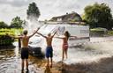 Kinderen laten zich in Kockengen nat spetteren door langsrijdende auto's in een straat die na hevige regenval onder water staat