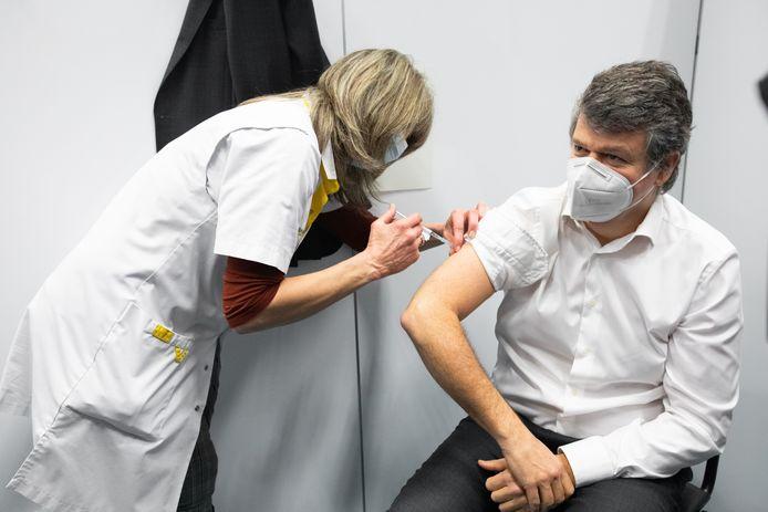 Ministers Somers krijgt zogezegd zijn coronavaccin toegediend.