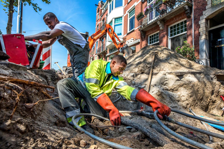 Medewerkers van Liander aan het werk in Amsterdam. De netbeheerder zegt dat door de overstap naar elektrische verwarming het stroomnet in delen van de hoofdstad bijna (of zelfs helemaal) vol zit. Beeld Raymond Rutting / de Volkskrant