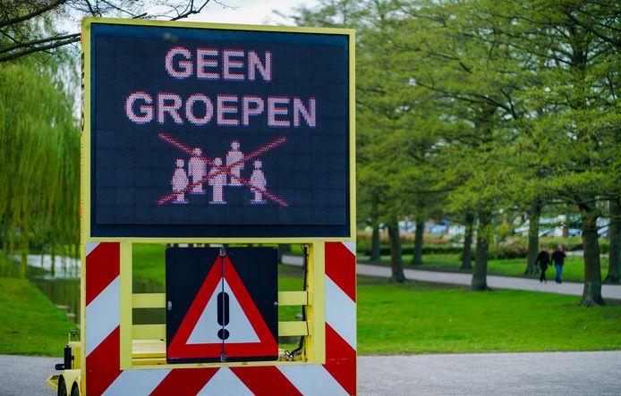 Een bord met de oproep aan mensen om bij drukte weg te blijven uit het Vroesenpark in Rotterdam.