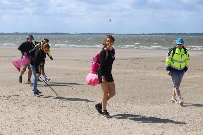Steef de Ruijter (midden) ruimt de Nederlandse kust op en bezocht donderdag het strand van Rockanje. Vrijwilligers hielpen haar, maar konden door de harde wind soms amper hun vuilniszak in bedwang houden.
