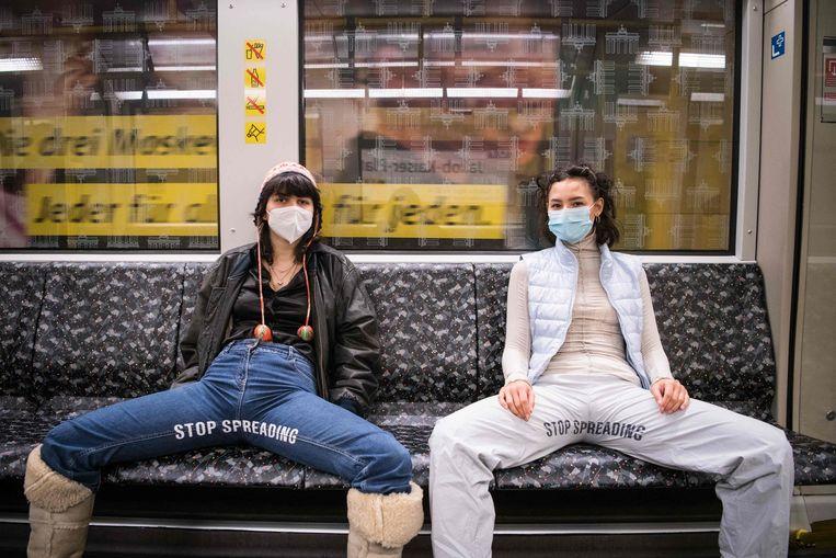 Feministisch protest van Elena Buscaino (r) en Mina Bonakdar tegen de neiging van mannen de ruimte voor zichzelf op te eisen: 'Stop Spreading',  in de metro in Berlijn, 5 februari 2021. Beeld AFP