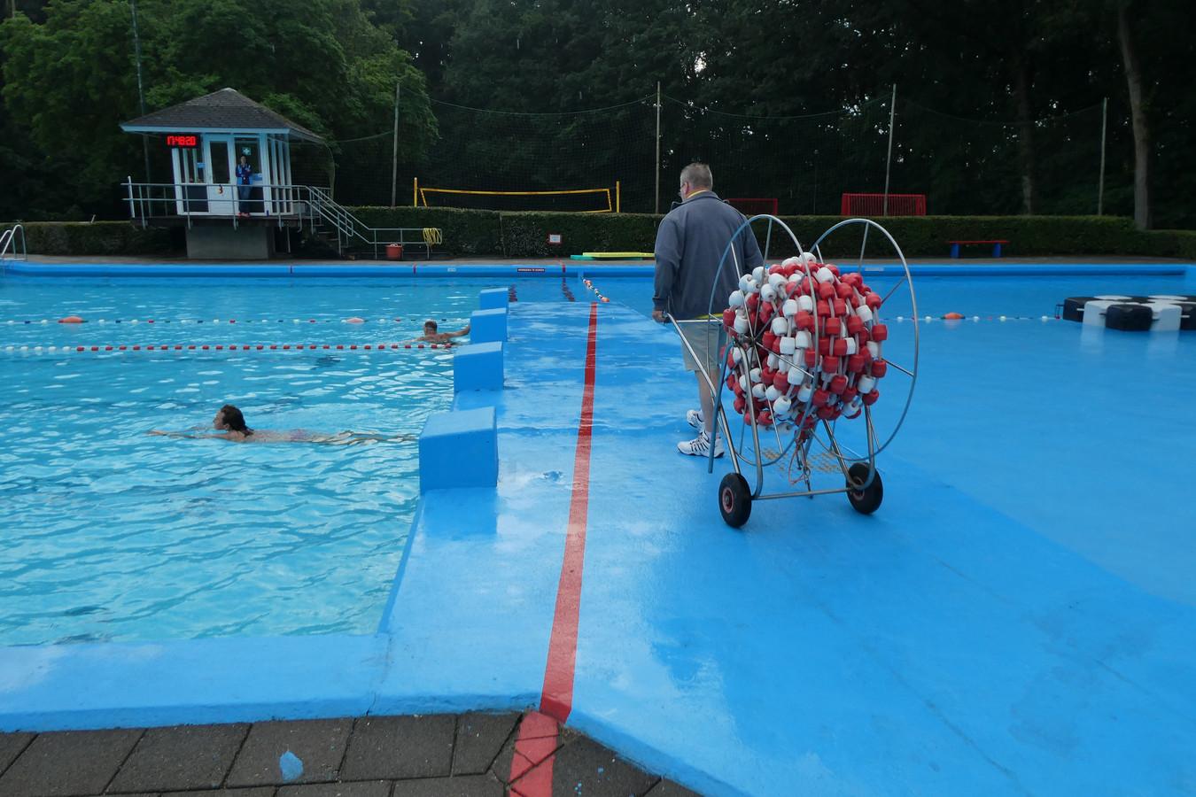 Edwin van den Oetelaar in de weer met de drijvende lijnen voor in zwembad Zegenwerp.