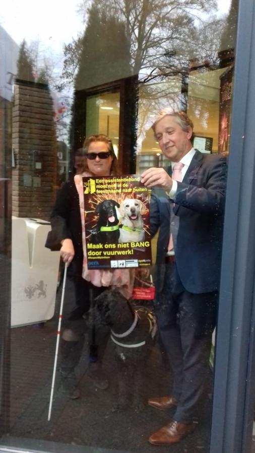 Francis Lotterman en de burgemeester hangen een poster op.