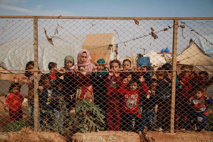 Syrische kinderen achter het hek van een vluchtelingenkamp, vlak bij de grens met Turkije.