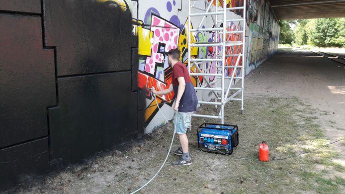 Mede-organisator Jan Pennings van graffitifestival Tunnel Vision 2.0 in Boxtel spuit de tunnel over het Duits lijntje zwart zodat 58 graffitikunstenaars er zondag aan de slag kunnen.