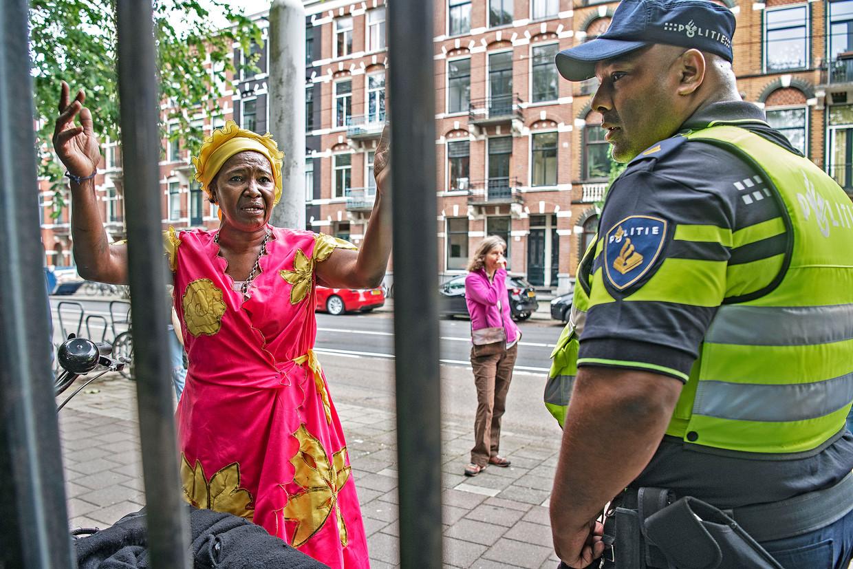 Grace Wijnhard beklaagt zich bij een politieagent dat ze niet het Amsterdamse Oosterpark in mag tijdens de Keti Koti-toespraak van burgemeester Halsema.  Beeld Guus Dubbelman / de Volkskrant