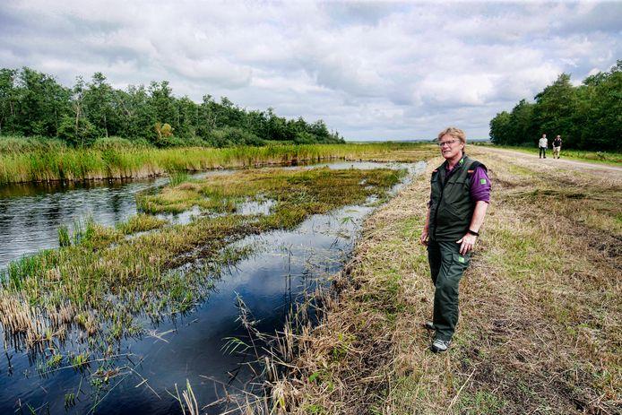 Boswachter Tineke Harlaar in de Westbroekse Zodden. Achter het moerasgebied schiet het broekbos hoog op. Rechts enkele wandelaars op het Bert Bospad.