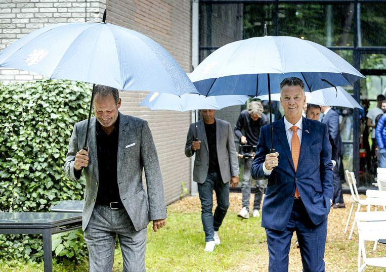 Louis van Gaal en assistent Danny Blind (links) trotseren het slechte weer in Zeist. Beeld ANP