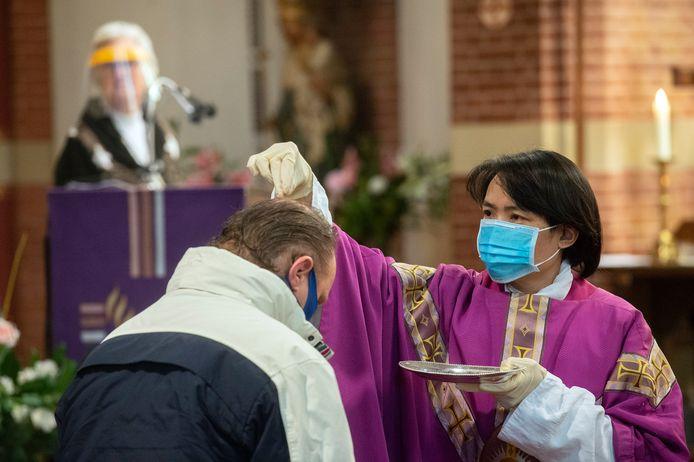 Kapelaan Thai Nguyen strooit in de Heilige Maria Hemelvaartkerk in Bavel as over de hoofden van gelovigen. Vanwege corona worden er geen askruisjes geplaatst.