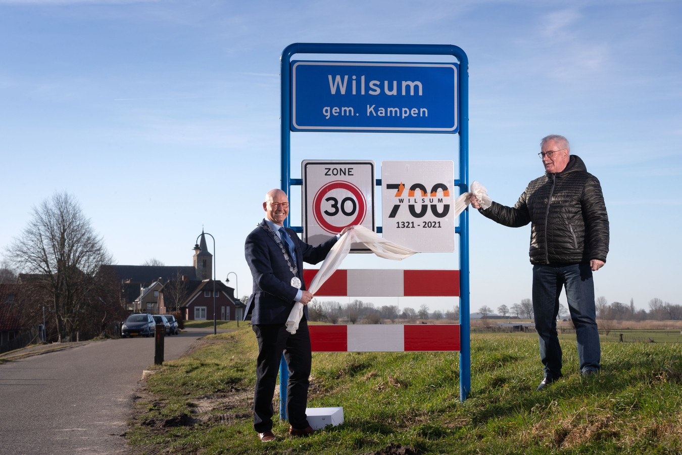 Samen met burgemeester Bort Koelewijn van Kampen, onthult Cor Wursten van Dorpsbelang Wilsum het bord voor het 700-jarig bestaan van Wilsum.