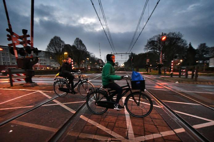 Leerlingen van basisschool, die de spoorwegovergang Aazelosestraat oversteken of er voor staan te wachten.