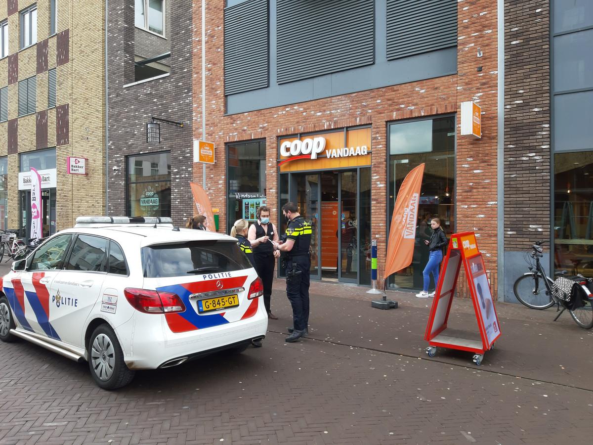 De politie en de bedrijfsleider van de Coop bespreken het incident