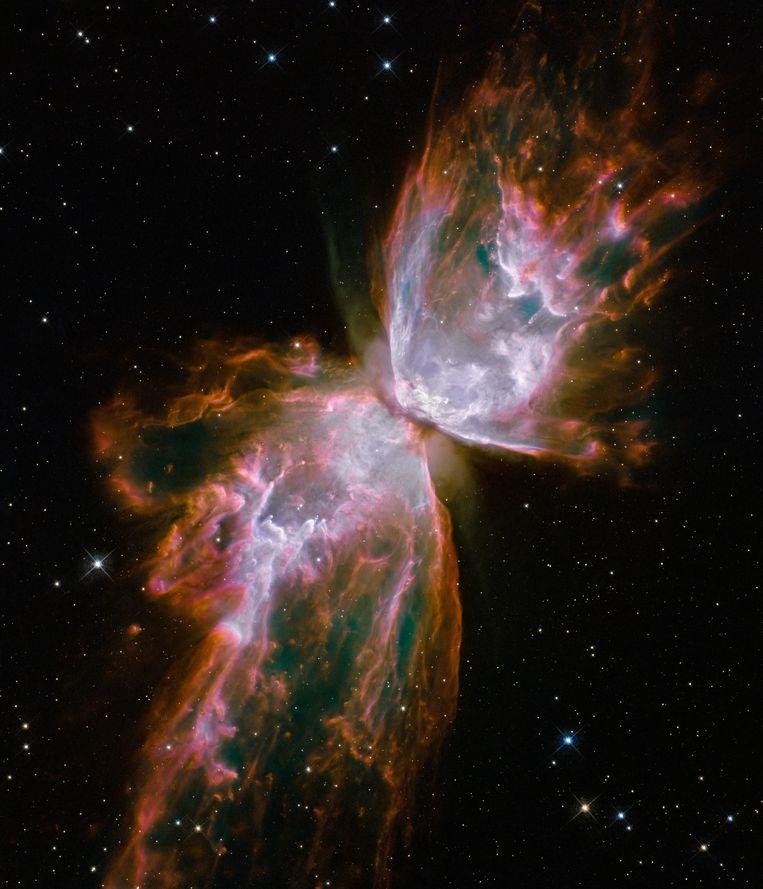 Het ziet eruit als een serene vlinder, maar schijn bedriegt. U kijkt hier naar een waar kosmisch inferno. Deze rode lagen gas racen met een snelheid van 950 duizend kilometer per uur door de kosmos en zijn zo'n 20 duizend graden Celsius heet. Al dat spul is afkomstig van de ster die in het midden huist (hier onzichtbaar) en die zijn buitenste lagen met veel geweld afstoot. Beeld Nasa & Esa