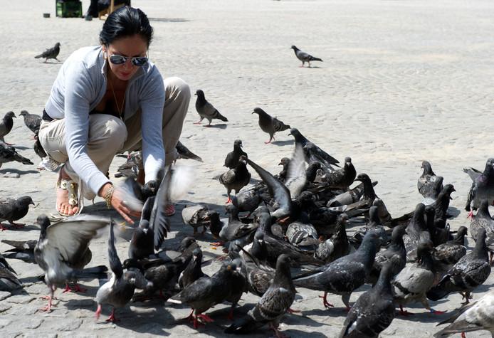 Een toerist tussen de duiven in Amsterdam, foto ter illustratie