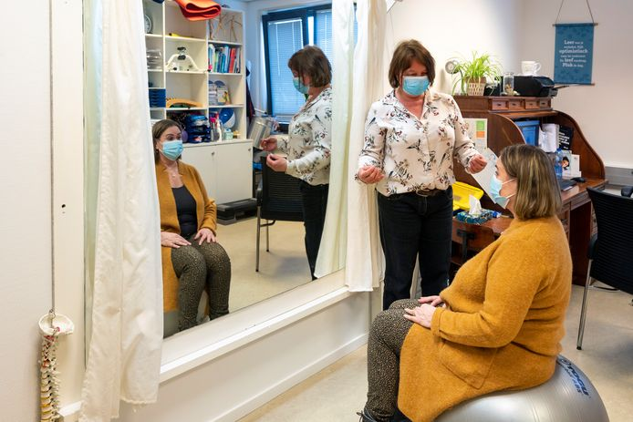 De zittende Tanya Zeeman werkt onder leiding van oefentherapeut Jacqueline van Baars aan haar houding.