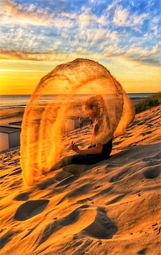 Onze dochter geeft een extra dimensie aan het palet van kleuren, veroorzaakt door de zonsondergang op het strand van Texel. In een wolk van stuifzand vangt zij deze kleurenpracht, waardoor een sprookjesachtige sfeer ontstaat.