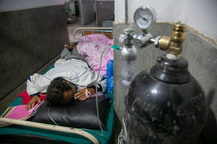 Een coronapatiënt ligt aan het zuurstof op de gang van een ziekenhuis in Kathmandu