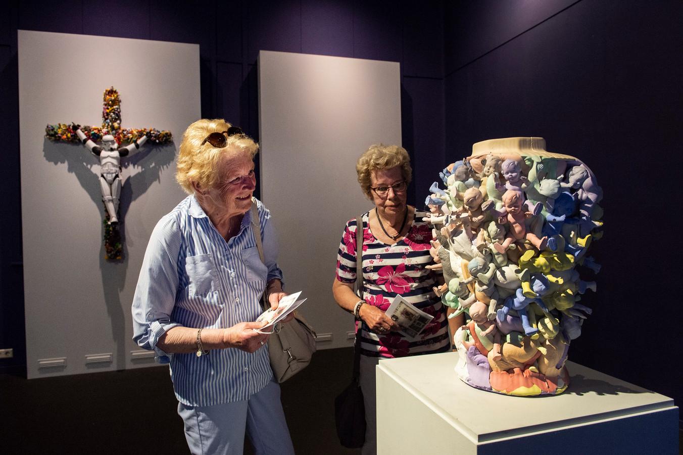 Agnes Johannesma (links) en Joke de Groot uit Amsterdam bekijken het werk van Geert Kollau.