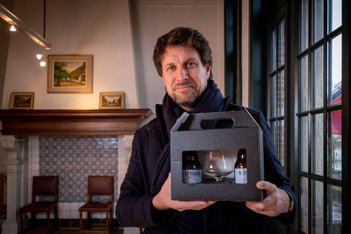 Voorzitter Dirk Frans van de Hooiktse dorpsraad toont een geschenkpakket met Ne Jutteneer biertjes.