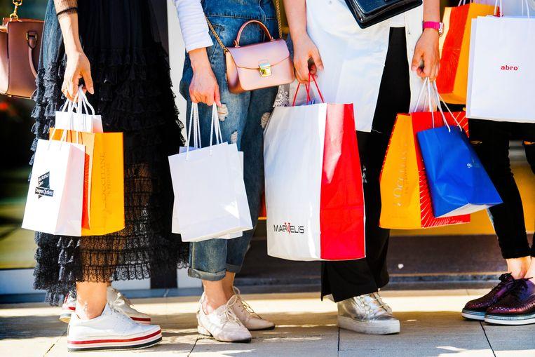 Heb je al genoeg kleding? Koop dan niet nog meer shirts, broeken en schoenen, zoals deze bezoekers van het Outlet Center Roermond, vinden aanhangers van de Fire-beweging.  Beeld ANP, Piroschka van de Wouw