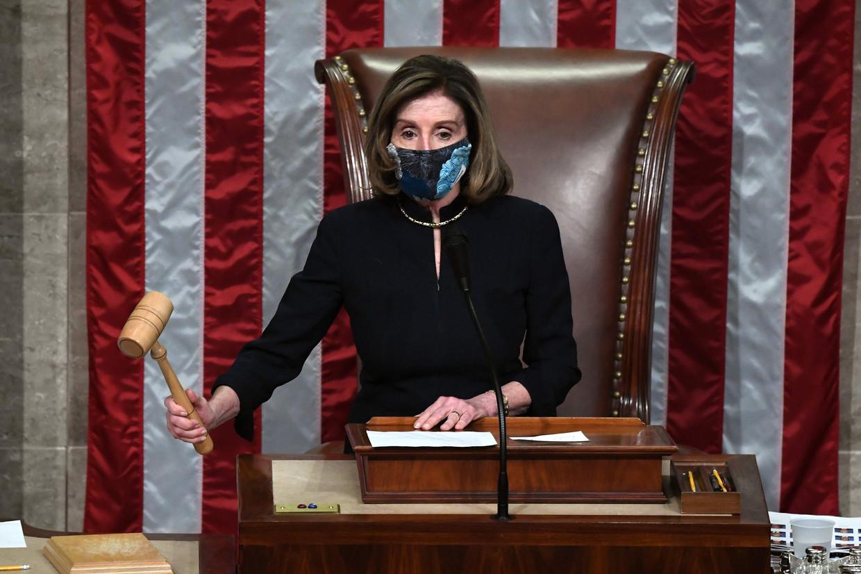 Voorzitter van het Huis van Afgevaardigden, Nancy Pelosi, sluit de stemming over Trumps tweede impeachment. Beeld AFP