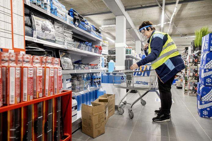 Een medewerker van Action verzamelt bestellingen in de winkel. Winkels mogen vanwege de coronamaatregelen nog niet open, maar online bestelde artikelen kunnen wel worden afgehaald. Klanten missen vooral het winkelen bij Action.