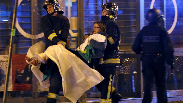 13 november 2015: brandweermannen brengen een gewond slachtoffer in veiligheid na het bloedbad in de Parijse concertzaal Bataclan. Beeld REUTERS