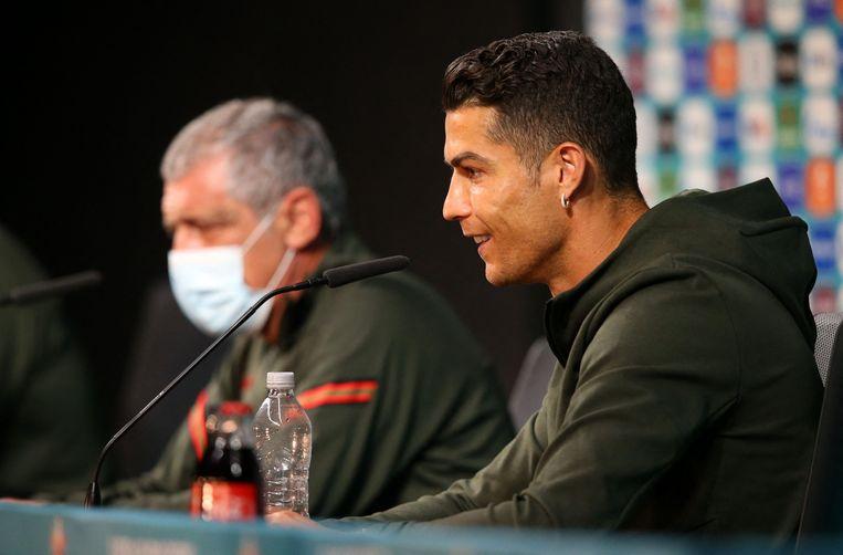 Cristiano Ronaldo heeft de colaflesjes (op de voorgrond) uit het zicht van de camera's gezet en houdt een flesje water in zijn hand.  Beeld AFP