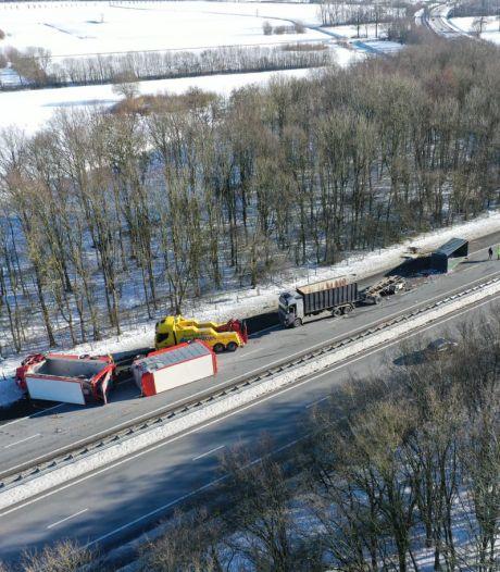 Grote ravage door botsende vrachtwagens op A50; kraan zet gekantelde truck en aanhangers recht