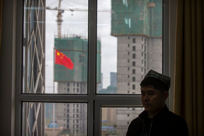 Een Oeigoerse leraar aan een raam in het islamitisch instituut in Xinjiang. Schuin achter hem wappert de Chinese vlag.