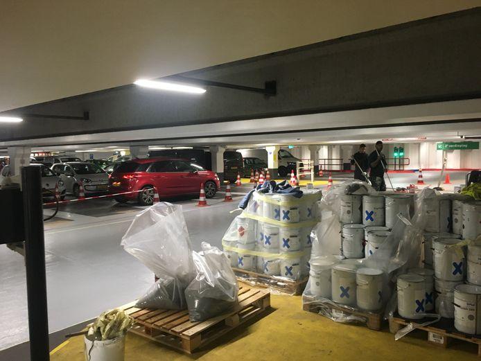 In de parkeergarage coaten werklieden  de vloer.