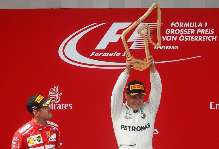Bottas aan het feest in Spielberg. Vettel kijkt toe als nummer twee. Beeld ap