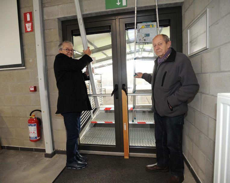Voorzitter Henri Vandervorst (l.) en ondervoorzitter Jean Matzeel barricaderen de deur.