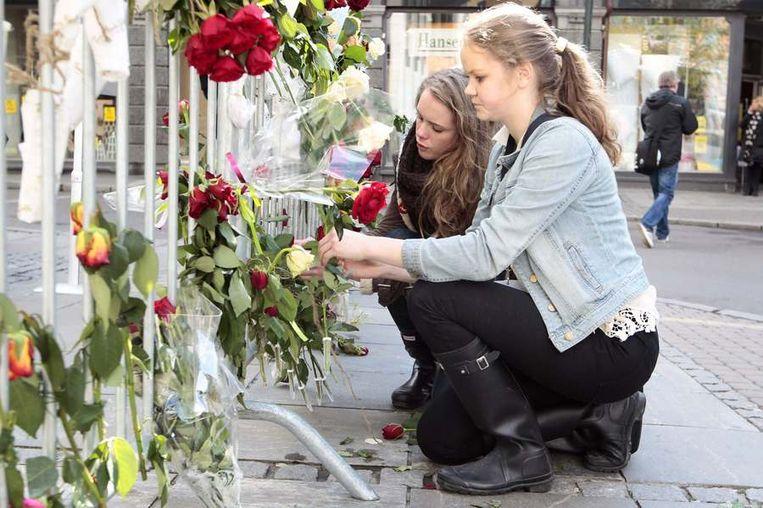 Meisjes binden rozen aan de dranghekken voor de rechtbank van Oslo. Beeld reuters