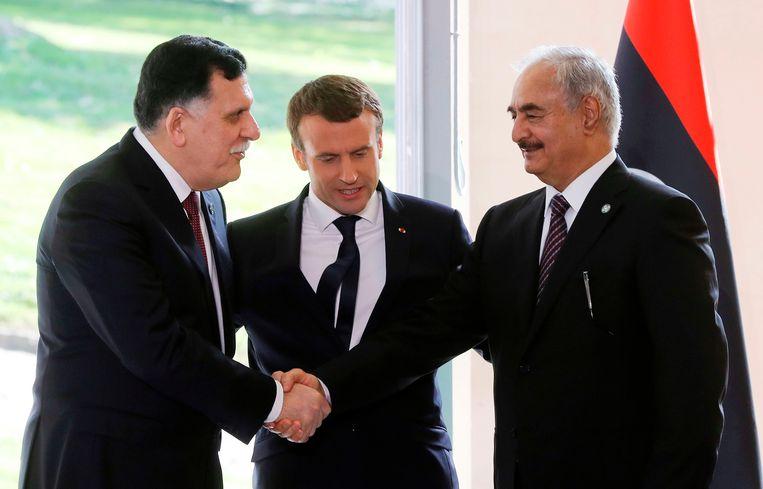 Premier Fayez Serraj (links) en generaal Khalifa Haftar (rechts) schudden elkaar de hand onder toeziend oog van de Franse president Emmanuel Macron. Beeld AFP