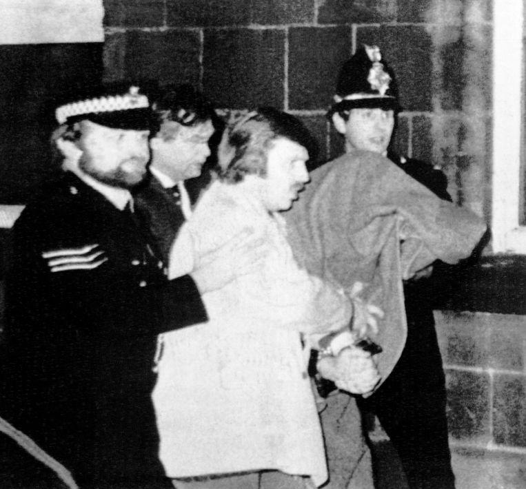 Peter Sutcliffe wordt na z'n arrestatie in 1981 weggebracht onder een deken. Beeld AP