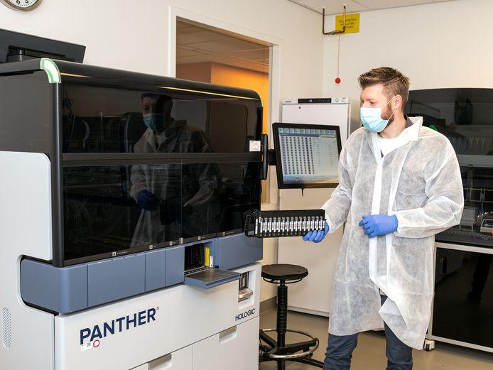 Roel Nijhuis, moleculair microbioloog, bij de Panther. Het apparaat dat grote volumes coronatesten weg kan werken.
