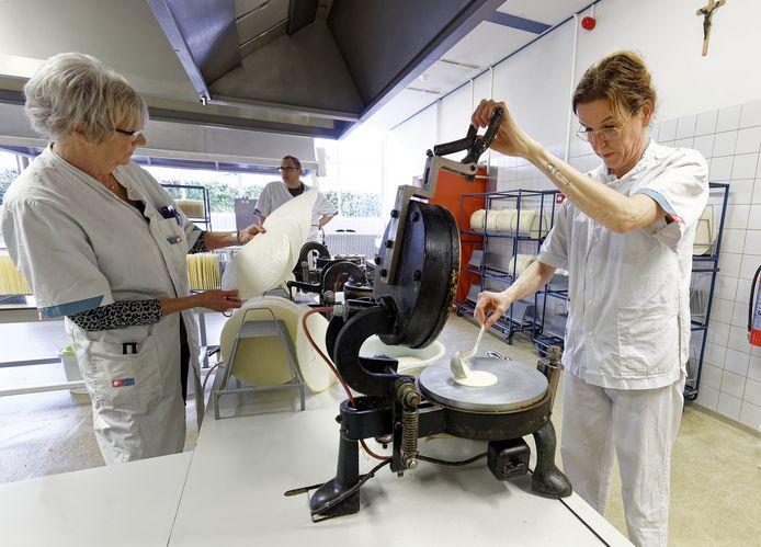 In de fabriek in Sint-Michielsgestel worden in bakpannen grote ronde hostieplaten gebakken. Die worden later versneden tot kleinere formaten.