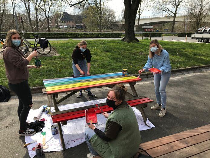 De jongeren verven de picknickbanken van jeugdhuis The Nooddle in regenboogkleuren.